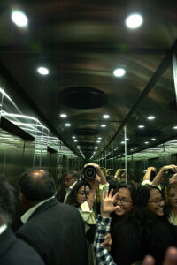people in a lift with camera